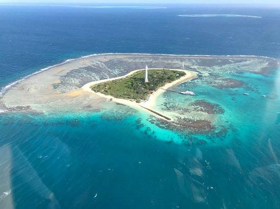survol en hélicoptère au dessus du lagon de nouvelle calédonie avec en arrière plan le phare amede